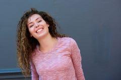 Muchacha adolescente de risa que se opone a la pared gris Foto de archivo libre de regalías