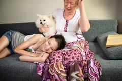 Muchacha adolescente de risa y su abuela con el perro Fotos de archivo libres de regalías