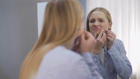 Muchacha adolescente decepcionada por el espejo reflectante de los problemas de piel de la cara, cambios hormonales almacen de video