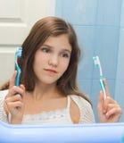 Muchacha adolescente a decidir entre los dos cepillos de dientes Imágenes de archivo libres de regalías