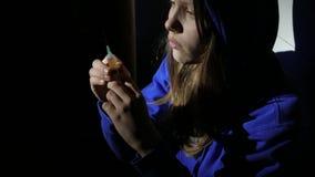 Muchacha adolescente del drogadicto adicto con una jeringuilla que se sienta en un piso y que piensa en algo 4k UHD metrajes