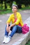Muchacha adolescente del estilo que se sienta en un parque Fotografía de archivo libre de regalías