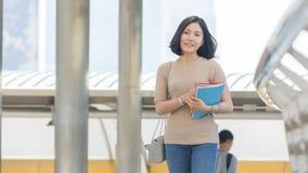 Muchacha adolescente del estudiante con el paseo del libro de la educación en al aire libre peatonal Imagen de archivo