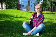 Muchacha adolescente del estudiante con la mochila que se sienta en parque Fotografía de archivo
