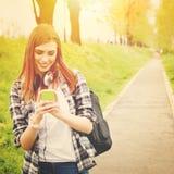 Muchacha adolescente del estudiante con mandar un SMS elegante del teléfono Imágenes de archivo libres de regalías
