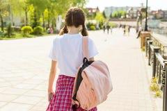 Muchacha adolescente del estudiante que camina abajo de la calle con la mochila De nuevo a escuela, visión trasera Imagen de archivo libre de regalías