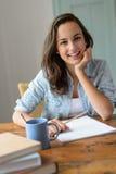 Muchacha adolescente del estudiante que estudia en casa la sonrisa Foto de archivo libre de regalías