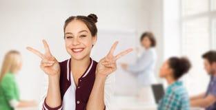 Muchacha adolescente del estudiante que muestra paz en la escuela Fotos de archivo libres de regalías