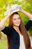 Muchacha adolescente del estudiante que sostiene los libros Imagen de archivo