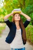 Muchacha adolescente del estudiante que sostiene los libros Foto de archivo libre de regalías