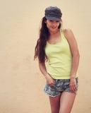 Muchacha adolescente del inconformista feliz que presenta en sombrero y pantalones cortos al aire libre Foto de archivo