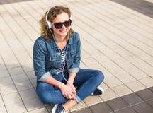 Muchacha adolescente del inconformista que sonríe y que escucha la música en ciudad Imagen de archivo libre de regalías