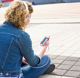 Muchacha adolescente del inconformista que sonríe y que escucha la música en ciudad Imagen de archivo