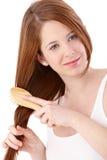 Muchacha adolescente del jengibre que peina el pelo largo Foto de archivo