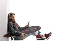 Muchacha adolescente del patinador con un longboard que se inclina contra una pared y Imagen de archivo libre de regalías