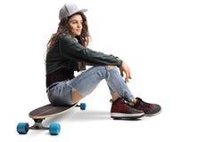 Muchacha adolescente del patinador que se sienta en un longboard Imágenes de archivo libres de regalías