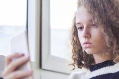 Muchacha adolescente del pelo rizado con el teléfono móvil por la ventana Fotos de archivo