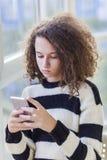 Muchacha adolescente del pelo rizado con el teléfono móvil por la ventana Foto de archivo