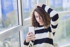Muchacha adolescente del pelo rizado con el teléfono móvil por la ventana Fotos de archivo libres de regalías