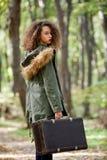 Muchacha adolescente del pelo rizado con la maleta retra en bosque del otoño Imagen de archivo