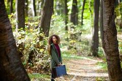 Muchacha adolescente del pelo rizado con la maleta retra en bosque del otoño Foto de archivo