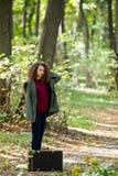 Muchacha adolescente del pelo rizado con la maleta retra en bosque del otoño Imágenes de archivo libres de regalías