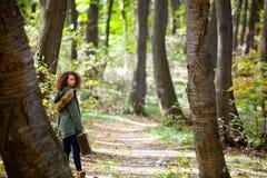 Muchacha adolescente del pelo rizado con la maleta retra en bosque del otoño Fotos de archivo