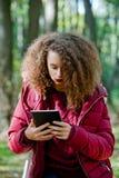 Muchacha adolescente del pelo rizado con la tableta digital en parque del otoño Foto de archivo