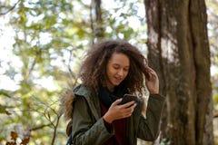 Muchacha adolescente del pelo rizado con smartphone en bosque del otoño Fotografía de archivo