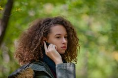 Muchacha adolescente del pelo rizado con smartphone en bosque del otoño Foto de archivo libre de regalías