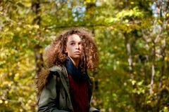 Muchacha adolescente del pelo rizado en bosque del otoño Fotos de archivo