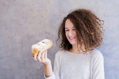 Muchacha adolescente del pelo rizado que come el cruasán Imagenes de archivo