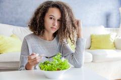 Muchacha adolescente del pelo rizado que come la ensalada Fotografía de archivo