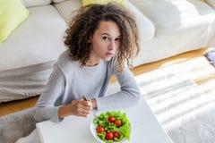 Muchacha adolescente del pelo rizado que come la ensalada Imágenes de archivo libres de regalías