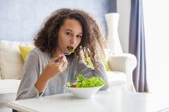Muchacha adolescente del pelo rizado que come la ensalada Foto de archivo libre de regalías
