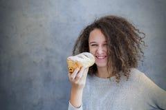 Muchacha adolescente del pelo rizado que sostiene el cruasán fresco Fotos de archivo