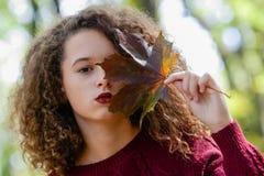 Muchacha adolescente del pelo rizado que sostiene la hoja de arce en bosque del otoño Foto de archivo libre de regalías