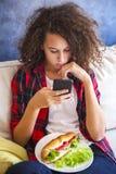 Muchacha adolescente del pelo rizado que usa el teléfono mibile y comiendo el bocadillo Foto de archivo libre de regalías