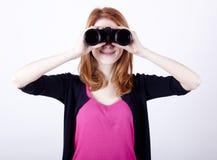 Muchacha adolescente del redhead con los prismáticos Imagen de archivo libre de regalías
