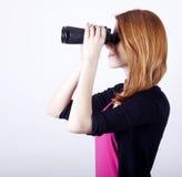 Muchacha adolescente del redhead con los prismáticos Fotos de archivo libres de regalías