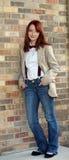 Muchacha adolescente del Redhead contra la pared de ladrillo Imagenes de archivo