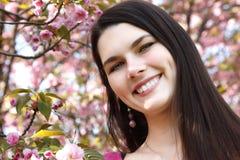 Muchacha adolescente del retrato de la primavera sobre tre japonés de la cereza del jardín de la naturaleza Fotos de archivo libres de regalías