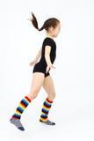 Muchacha adolescente delgada que hace danza de la gimnasia en el salto en blanco Imagen de archivo libre de regalías