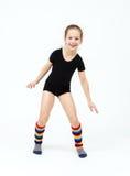 Muchacha adolescente delgada que hace danza de la gimnasia en el salto en blanco Foto de archivo libre de regalías