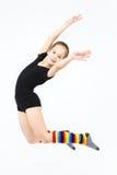 Muchacha adolescente delgada que hace danza de la gimnasia en el salto en blanco Fotos de archivo libres de regalías