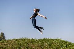 Muchacha adolescente delgada vestida en vaqueros y un salto negro del top alto sobre hierba verde contra el cielo imagenes de archivo