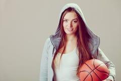 Muchacha adolescente deportiva en la capilla que lleva a cabo baloncesto Imagenes de archivo