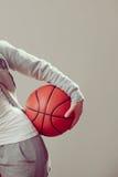 Muchacha adolescente deportiva que lleva a cabo baloncesto con una mano Imagen de archivo