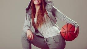 Muchacha adolescente deportiva que lleva a cabo baloncesto con una mano Fotos de archivo libres de regalías