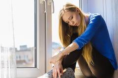 Muchacha adolescente deprimida triste que se sienta en travesaño de la ventana Fotografía de archivo